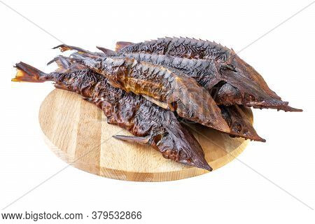 Smoked Sterlet Or Sturgeon Fish. Smoked Dilicates Sterlet Sturgeon Fish On A Wooden Board. Few Smoke