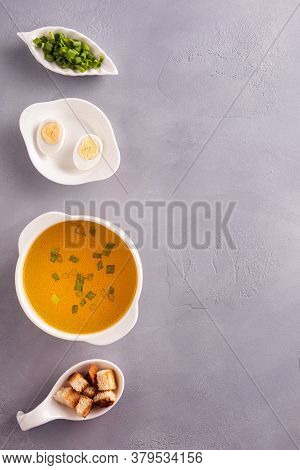 Vertical Background With Row Of White Crockery With Chicken Bouillon, Chopped Green Onion, Croutons