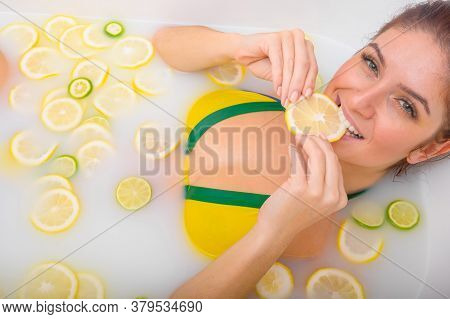 Beautiful Young Red-haired Woman Takes A Bath With Milk And Citrus Fruits. Portrait Of Caucasian Smi