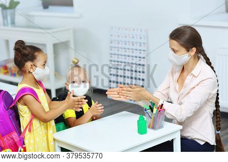 The Teacher Helps And Explains To Children How To Disinfect Their Hands. A Teacher And Students In M