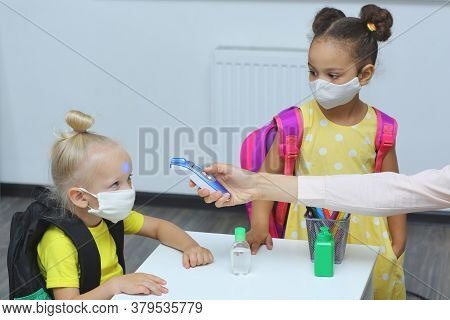 A Teacher In The Classroom Measures The Temperature Of Students. Childrens In Medical Masks Waiting