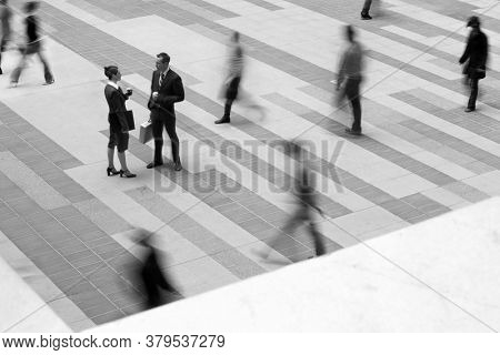 Black and White photo of two business people talking in blurred crowd