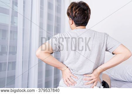 Young Man Suffering Back Pain From Uncomfortable Bed. Healthcare Medical Or Daily Life Concept.