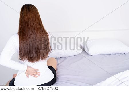 Young Woman Suffering Back Pain From Uncomfortable Bed. Healthcare Medical Or Daily Life Concept.