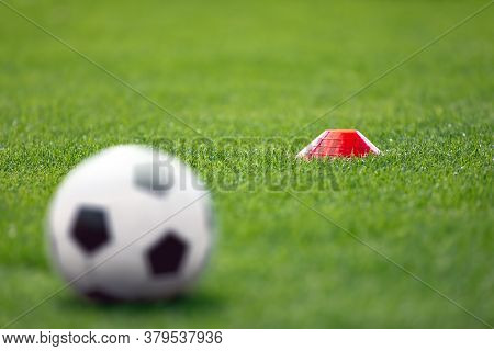 Single Red Soccer Training Marker And Blurred Soccer Ball On Grass Lawn. Fresh Grass Soccer Field