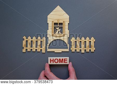 Model Of A Wooden House. Word 'home' On Wooden Block. Male Hand, Wooden Fence. Copy Space. Business