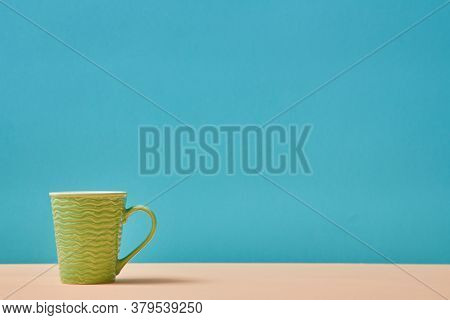 Utensils. Teacup. Tableware Concept. Green Cup With Wavy Decor. Vessel For Drink. Empty Mug. Blue Ba