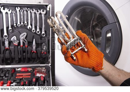 Repair Of Washing Machines. Hand Of A Repairman With A Turbulent Electric Heater Covered With A Coat
