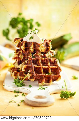 Homemade low carb zucchini waffles on white wooden board on yellow background. Concept of keto diet food.