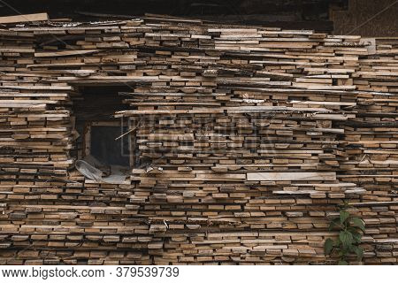 A Tall Woodpile Consisting Of Many Small Logs Stacked Around A Small Square Window.