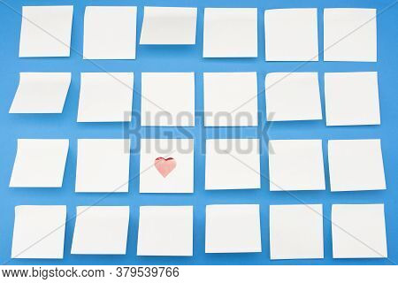 Lots Of Blank Yellow Eidin Stickers With Hearts On Blue Background. View From Above