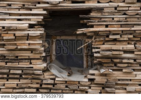 A Tall Woodpile Consisting Of Many Small Logs Stacked Around A Small Square Window Located In The Ce
