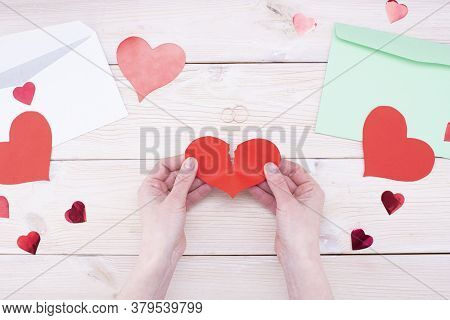 Female Hands Hold A Broken Heart With Wedding Rings On A Wooden Table. Marriage Problems, Divorce