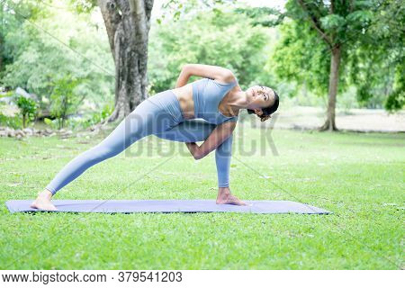 Asian Attractive Young Woman Doing Yoga In An Elegant Posture, In The Green Park, Concept To People