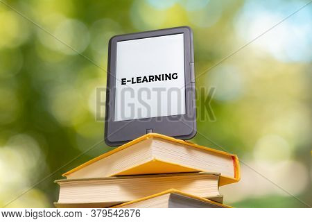 E-learning And Reading. E-book Reader Is At The Top Of The Stack Of Books. The Park Is Blurred In Th