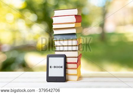 Reading. E-book Reader And A Stack Of Books. The Park Is Blurred In The Background. Concept Of Educa