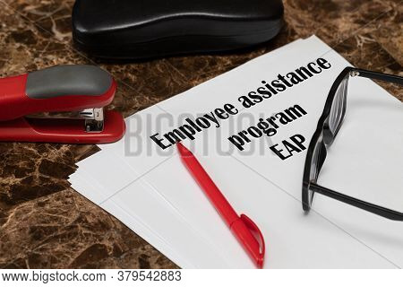 Eap Employee Assistance Program. The Text Is Written On White Paper, Next To A Red Pen, A Hole Punch