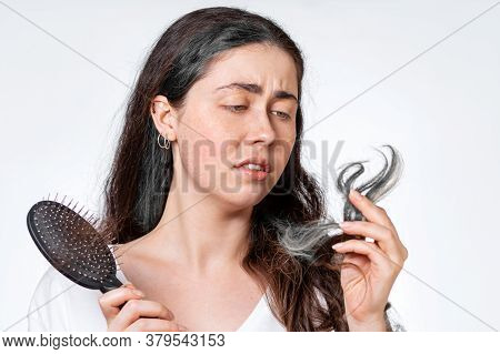 A Saddened Brunette Woman Holds A Comb With Her Hair Falling Out And Looks At The Gray Tips Of Her H