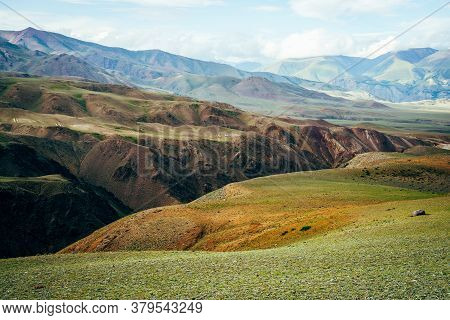 Awesome Vivid Mountain Landscape With Deep Gorge. Multicolor Mountains, Green Pass And Ravine In Sun