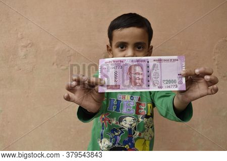 Delhi, India-march 21 2019:cute Little Boy Holding 2000 On Indian Street, Demonetisation Concept