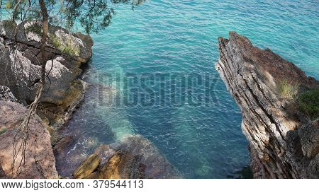 View Over The Sea From The Shore, Rocks Close-up. Azure Water, Stormy Waves. Pine Branches.