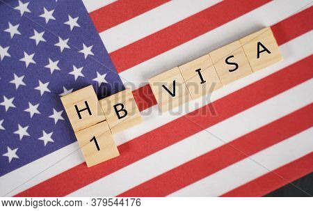 Concept Of H1b Visa For Foreign Workers Showing Wooden Letters With Us Or United States Flag As Back
