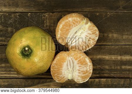 Peeled Tangerine In A Wooden Rustic Table With One Whole And The Peel Separated - Top View
