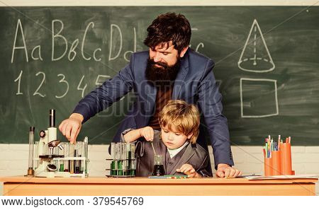Student Doing Science Experiments With Microscope In Lab. Father And Son At School. Using Microscope