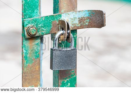 Closed And Locked Door Grill With Silver Padlock. A Metal Lock On Hinges Hangs In Close-up On The Gr