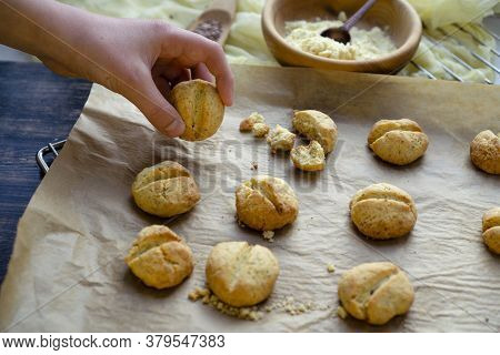 Shortbread Cookies With Lemon And Corn Flour On Parchment Paper With The Hand Of A Guy Taking One Pi