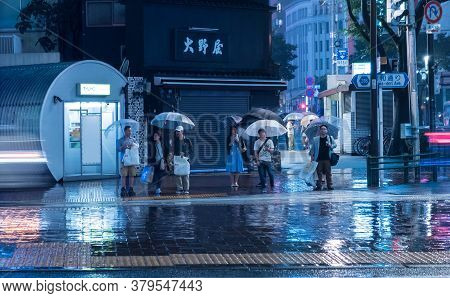 Tokyo, Japan - June 10, 2018: People In The Rain Standing At The Crosswalk. Rainy Evening In Tokyo,