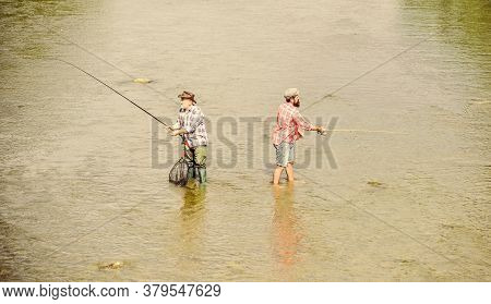 Happy Fisherman With Fishing Rod And Net. Hobby And Sport Activity. Male Friendship. Father And Son