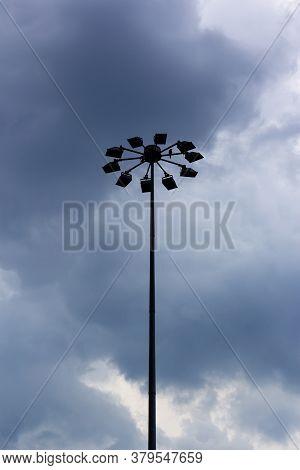 Modern Lighting Mast With Lanterns Against The Dark Sky With A Sitting Bird. Street Lights. The Big
