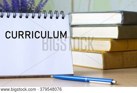 Curriculum - A Word In A Notebook Against The Background Of Old With A Pen. Education Concept.