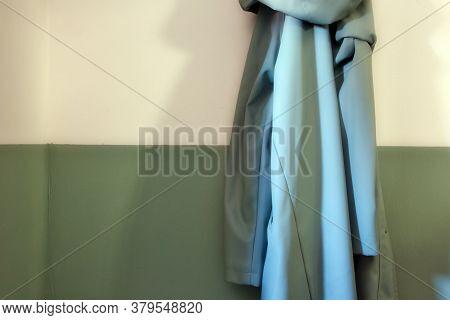 Green Retro Raincoat Hanging On A Half White Half Green Wall In Modern Hallway Of A House. Modern St