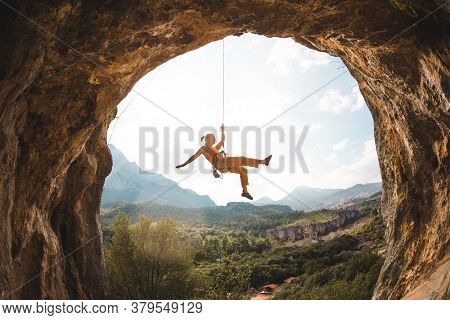 Rock Climber Hanging On A Rope. A Woman Climbs A Rock In The Shape Of An Arch. The Girl Climbs In Th