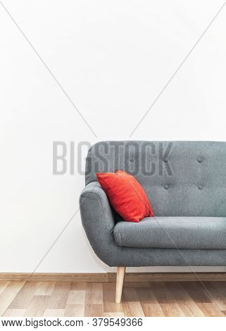 Modern Gray Couch With Red Pillows On Wooden Tiled Floor - Office Furniture, White Wall - Space For