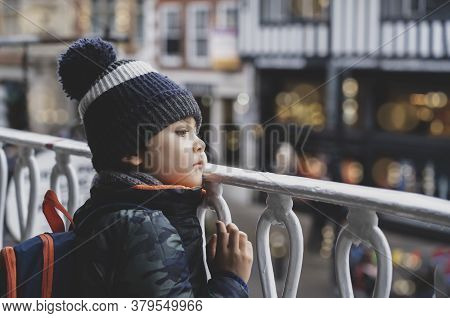 Candid Shot Kid Looking Out On The Road With Blurry Christmas Light At The Shop On Street, Child Wit