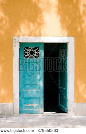 Open Green Double-barrelled Doors With Bars Against The Yellow Wall
