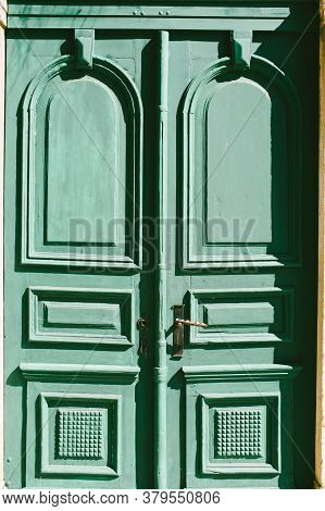 Close-up Of Closed Green Doors Decorated With Squares And Rectangles With A Metal Handle.