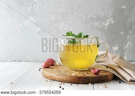 Cup Of Homemade Beef Bone Broth On White Wooden Background With A Copy Of Space.