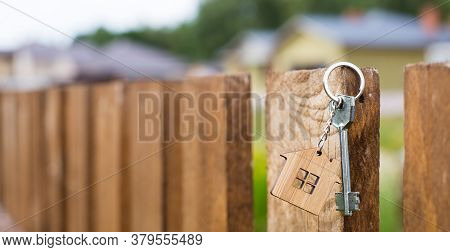 Wooden Pendant Of A House And Key. Background Of Fence And Cottage. Dream Of Home, Building, Design,