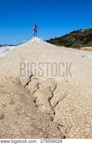 A Beautiful Slender Girl Stands On Top Of An Inactive Mud Volcano. Travel, Desert, Geological Landsc