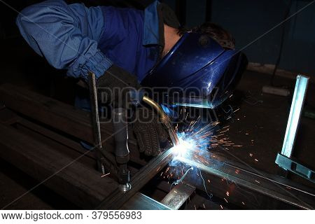 Welding. Electric Arc Welding. The Worker Welding Two Iron Corners.