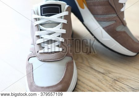 New Mens Sneakers Stand On A Gray Laminate. Selling Sports Shoes Online. Fitness Shoes In A Club Or