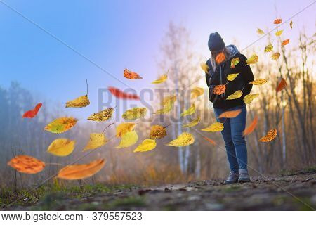 Sad Young Woman Walking Through Autumn Forest At Sunset