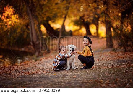 Two Little Girls Walking Golden Retriever In Autumn Park. The Friendship Of Children And Dogs.
