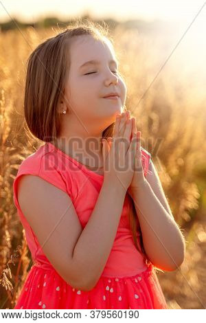 Little Girl Folded Her Hand And Close Your Eyes In Praying, Dreaming In Field Outdoors. Child Prayin