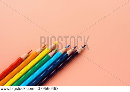 Colored Pencils On Pink Paper, Flat Lay. Uneven Set Of Rainbow Pencils, Copy Space. Pencils Lie Diag