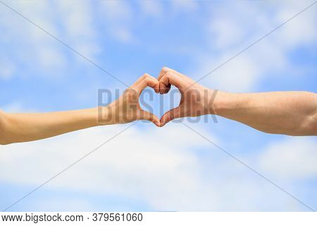 Love, Friendship Concept. Girl And Male Hand In Heart Form Love Blue Sky. Female And Man Hands In Th